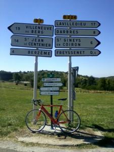 Vélo posé devant les panneaux indiquant les circuits de l'Ardéchoise : les Gorges, La Méridionale, La Chataîgne