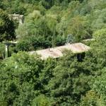 Vue du bâtiment dans le hameau, entouré de végétation